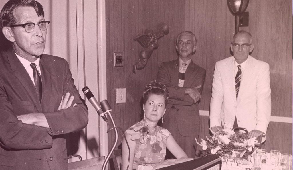Photo Ancienne d'un homme les bras croisés parlant dans un micro. 2 hommes et une femme le regardent