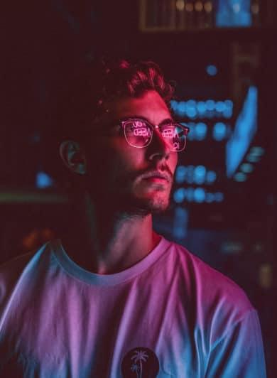 Jeune homme devant un magasin. Ambiance colorée rose et bleu