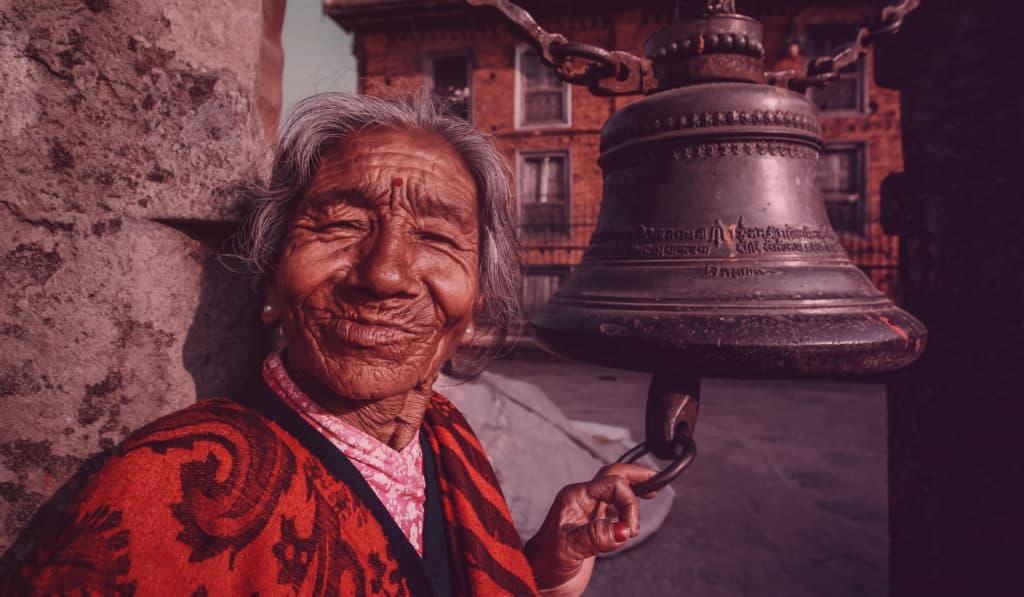 Vielle dame souriant à coté d'une cloche en amérique du sud